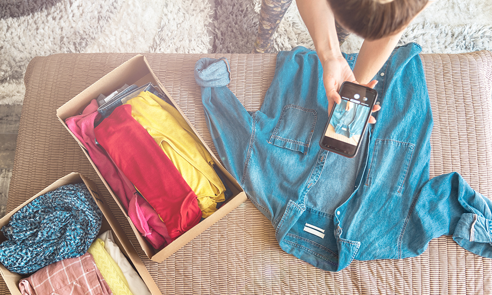 Woman photographing denim shirt to resell it